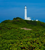 Lighthouse on green hill Stock Photo