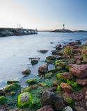 Lighthouse with green rocks in the foreground Royalty Free Stock Photos