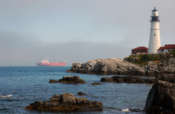 Lighthouse Guides Oil Tanker Vessel Out of Fog Royalty Free Stock Photography