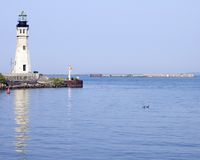 Lighthouse At Harbor Entrance Royalty Free Stock Images