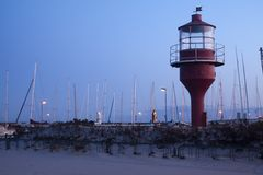 Lighthouse. In harbour while the sun is rising Stock Photo