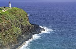 Lighthouse on an Hawaian cliff. An old white lighthouse with a red roof on a remote cliff over a calm ocean in the Hawaii islands in daylight. Concept for Stock Image