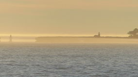 Lighthouse in the Haze with Sailboat Royalty Free Stock Images