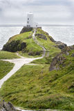 Lighthouse on hill overlooking Irish Sea. Lighthouse on hill overlooking Irish Sea, Llanddwyn Island, Anglsey, Wales royalty free stock image