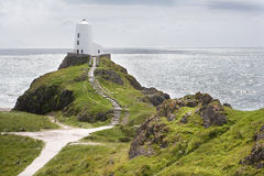 Lighthouse on hill overlooking Irish Sea. Lighthouse on hill overlooking Irish Sea, Llanddwyn Island, Anglsey, Wales stock photo