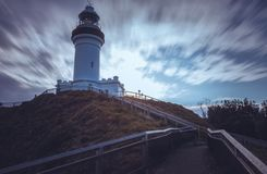 Lighthouse on hill of shore under clouds royalty free stock photos