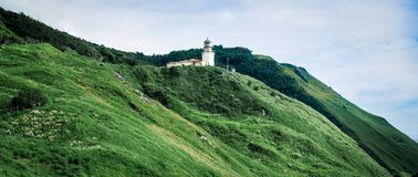 Lighthouse on the hills. Lonely lighthouse stading on emerald hills of Tatar Strait shore, Sakhalin Stock Image