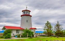 Lighthouse in Homer Alaska. Homer, Alaska, USA - June 28, 2017 Homer Lighthouse sits on the edge of Kachemak Bay under cloudy skies in Homer, Alaska Stock Photo