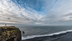 Lighthouse in Iceland. Next to Black Sand Beach. Landscape with Stormy Clouds and Ocean Water Royalty Free Stock Images