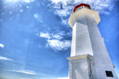 Lighthouse Illuminated by the Sun. A lighthouse glows against bright blue sky and sunlight Royalty Free Stock Image