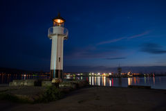 Lighthouse. A lighthouse illuminating at night stock photo