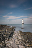 Lighthouse. An incoming tide down on the rocks near Brougham lighthouse Royalty Free Stock Photography