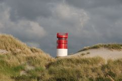 Lighthouse on Island Dune, Helgoland, Germany. Lighthouse at Düne with grass and dunes in the foreground and dark sky in the background Stock Images