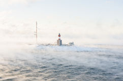 Lighthouse on an isle in misty sea Royalty Free Stock Photo