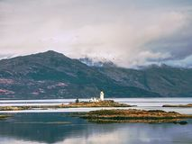Lighthouse on Isle of Ornsay, the southern side of Isle of Skye, Scotland. Trade ship at rocky island,. Mountains in background Stock Image