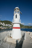 Lighthouse in Kash with blurred background. Lighthouse in Kash shot on sunny day with blue sky and green mountains with residential area on backgrouns Royalty Free Stock Photo