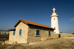 A lighthouse and a keeper shed in Paphos Archaeological Park, Cyprus. A lighthouse and a keeper house view in Paphos Archaeological Park, Cyprus royalty free stock photography