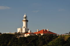 Lighthouse and keepers accomodation. White lighthouse with red roofed keepers accomodation on hilltop with blue sky and light cloud Royalty Free Stock Photo