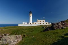 Lighthouse and keepers house on grassy hillside along the sea. Rua Reidh Lighthouse with keepers house and walls on grassy hillside along the coast. Rocks in the stock image