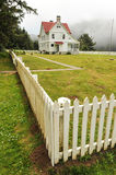Lighthouse keeps house surrounded by fence Royalty Free Stock Image