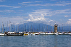 Lighthouse on lake Garda, Italy. View on the lighthouse and yachts with mountains on background, Lake Garda, Italy Royalty Free Stock Images