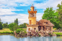 Lighthouse on the lake in  hamlet Queen Marie Antoinette`s esta. VERSAILEES, FRANCE- JULY 02, 2016 : Lighthouse on the lake in  hamlet Queen Marie Antoinette`s Royalty Free Stock Images