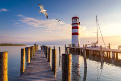 Lighthouse at Lake Neusiedl at sunset near Podersdorf with sea gulls flying around the lighthouse. Burgenland, Austria.  stock images