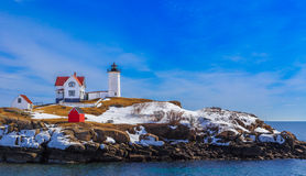 Lighthouse. Landscape with rocky shore and winter snow. Nubble , York, Maine Royalty Free Stock Photos