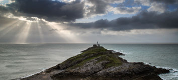 Lighthouse landscape with stormy sky over sea with rocks in fore Royalty Free Stock Photography