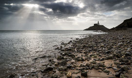 Lighthouse landscape with stormy sky over sea with rocks in fore Stock Photography