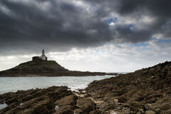 Lighthouse landscape with stormy sky over sea with rocks in fore Royalty Free Stock Images