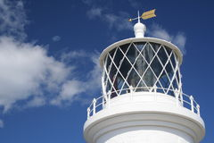 Lighthouse Lantern House. Close-up of white lighthouse tower against a deep blue summer sky Royalty Free Stock Image