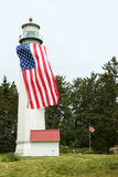 Lighthouse with large American flag. Westport, WA, USA June 11, 2017: Upper portion of the Westport Lighthouse with a large American flag hung vertically from Stock Photography