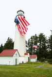 Lighthouse with large American flag. Westport, WA, USA June 11, 2017: Upper portion of the Westport Lighthouse with a large American flag hung vertically from Royalty Free Stock Image