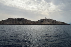 Lighthouse on Lefkada cape - the most southern point of Lefkada Island, Greece. Seen from the see the dark silhouette of Lefkada Cape with lighthouse on it Royalty Free Stock Images