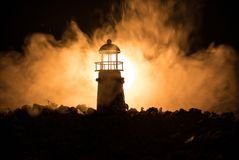 Lighthouse with light beam at night with fog. Selective focus Royalty Free Stock Photos