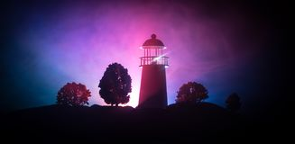 Lighthouse with light beam at night with fog. Old lighthouse standing on mountain. Table decoration. Toned background. Artwork decoration. Lighthouse with light stock photo
