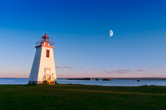 Lighthouse in the light from moon and sun Royalty Free Stock Image