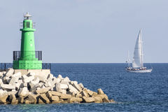 Lighthouse lined with sailboats