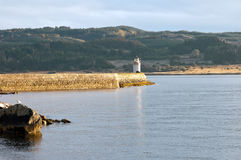 Lighthouse on loch fyne. A lighthouse lighting the way along the rocky shores of loch fyne Royalty Free Stock Photo