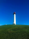 Lighthouse, Long beach, CA, USA. White Lighthouse with red top on the green hill Against the background of the blue sky Stock Image