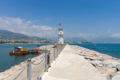 The lighthouse and long pier at the entrance to the sea port of Alanya Stock Photo