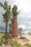 Lighthouse. Majestic lighthouse on the beach with an ominous cloudy sky royalty free stock photos