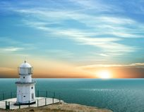 Lighthouse in a marine cape. On a sunset Stock Image