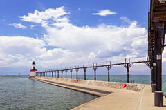 Lighthouse at Michigan City, Indiana. An elevated metal catwalk leads to the East Pierhead Lighthouse at Michigan City, Indiana on a partly cloudy summer stock images