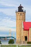 Lighthouse and the Mighty Mac. The Old Mackinac Point Lighthouse is backed by the Mackinac Bridge, one of the world's great suspension bridges connecting Stock Photo