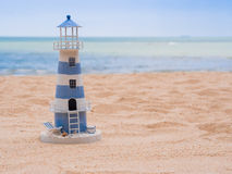 Lighthouse model on the sand beach. Blue sky and sea background Royalty Free Stock Photo