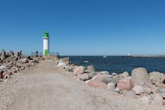 Lighthouse on the moll and a man near it, yacht in the sea Royalty Free Stock Photography