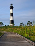 Lighthouse in the morning sun. A well-worn boardwalk provides a trail through the marshland surrounding the Bodie Island Lighthouse in the Outer Banks of North Royalty Free Stock Image