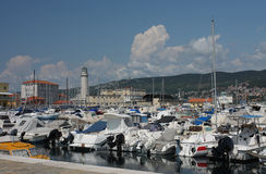 Lighthouse, motor boats and sailboats in harbor in Trieste, Ital Stock Photography